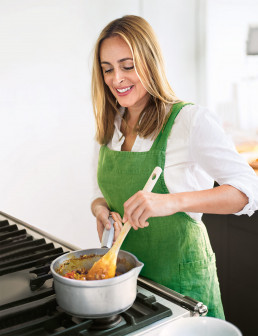 Amelia Freer cooking with green apron
